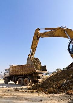 De baggerwagen en de kipwagen werken aan de bouw.