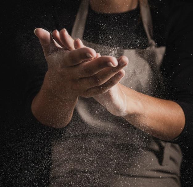 De bakker van de close-up schoonmakende handen van bloem