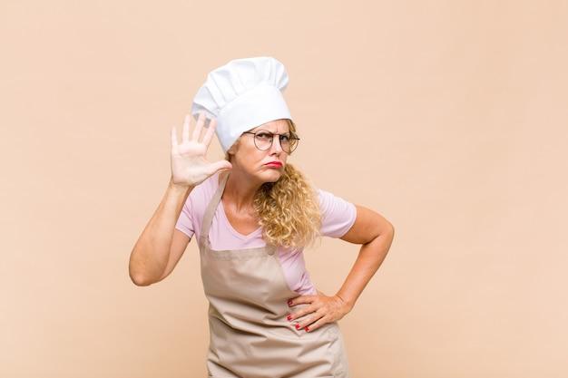 De bakker van middelbare leeftijd en vriendschappelijk glimlachen kijkt, nummer vijf of vijfde met vooruit hand tonen, aftellend