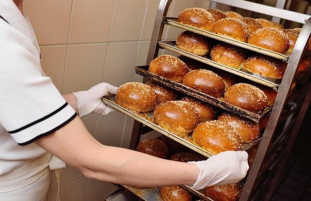 De bakkerijarbeider die van de vrouw een dienblad van verse ronde broodjes voor burgers met sesamzadenclose-up houdt