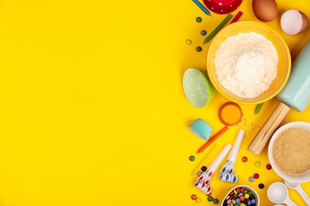 De bakselverjaardag cupcakes ingrediënten op gele vlakke achtergrond, legt