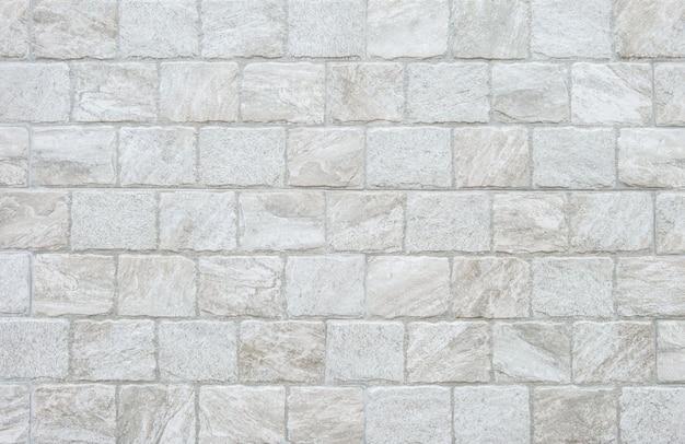 De baksteenpatroon van het close-upoppervlak bij grijze de textuurachtergrond van de steenbakstenen muur