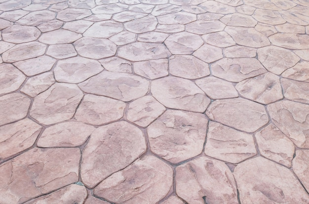 De baksteenpatroon van het close-upoppervlakte bij de oude rode vloer van de steenbaksteen bij de achtergrond van de wegtextuur