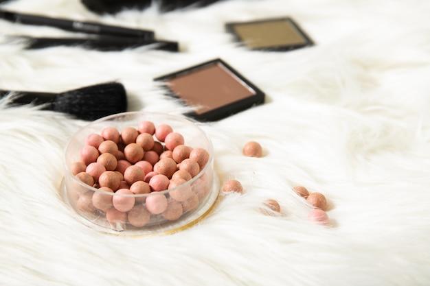 De bal bloost en decoratieve schoonheidsmiddelen op een witte achtergrond