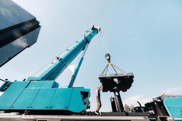 De ballast wordt door een onherkenbare arbeider op een grote blauwe autokraan gemonteerd en is bereid om op een terrein te werken Premium Foto