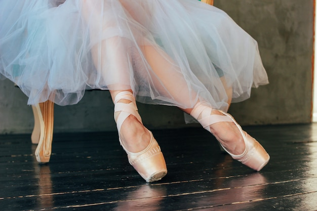 De ballerina balletdanser in pointe shous zittend op de klassieke stoel