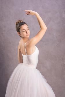 De ballerina die van het zijaanzicht over haar schouder kijkt