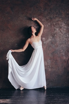 De balletdanserballerina in mooie dunne vliegende witte kleding stelt in donkere zolderstudio