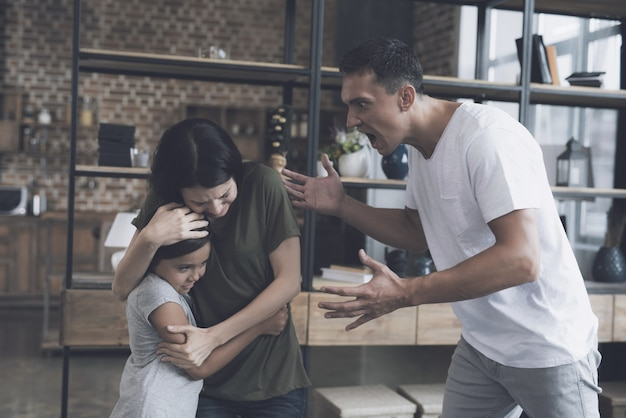 De bang gemaakte moeder beschermt dochter tegen slechte vader