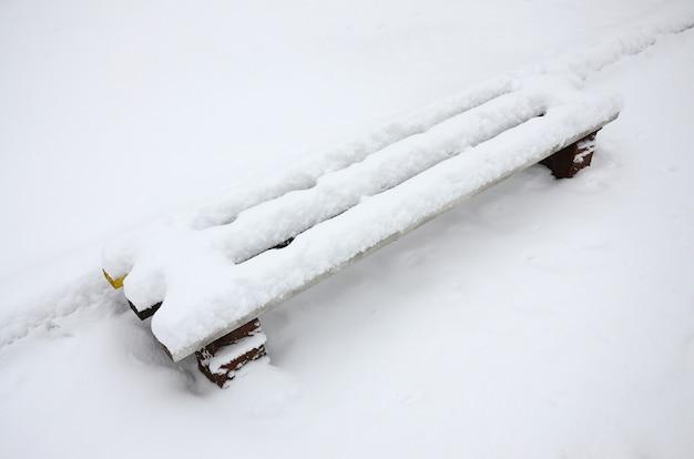 De bank, bedekt door een dikke laag van een muur, bevindt zich op een met sneeuw bedekt platform
