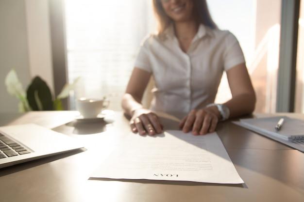 De bankarbeider die leningsovereenkomst, nadruk op document aanbieden, sluit omhoog