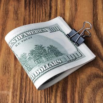 De bankbiljetten van de dollar liggen bij houten achtergrond.