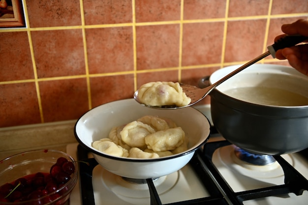 De banketbakker haalt gekookte dumplings uit kokend water in een vergiet. proces van het koken van dumplings stap voor stap. close-up, voedselachtergrond.