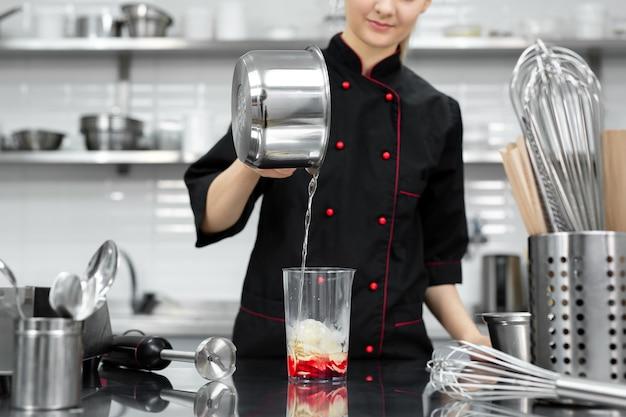 De banketbakker klopt de rode spiegelglazuur voor de cake met een blender.