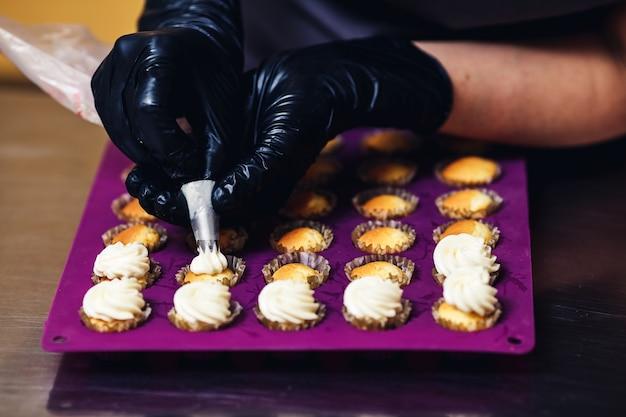 De banketbakker perst room uit een spuitzak op muffins in de keuken. het concept van thuis bakken, taarten maken.