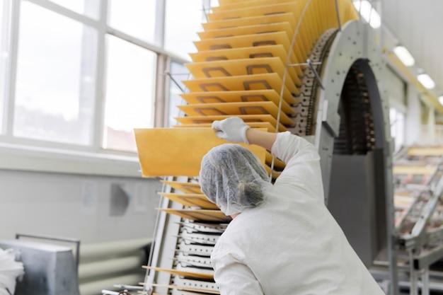 De banketbakker-technoloog controleert de kwaliteit van het bakken van wafels op de transportband in de winkel van de zoetwarenfabriek