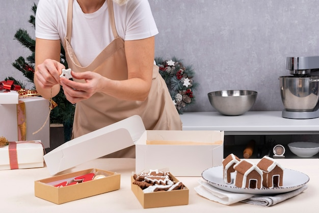 De banketbakker verpakt kerstmissnoepjes in dozen. peperkoek koekjes.