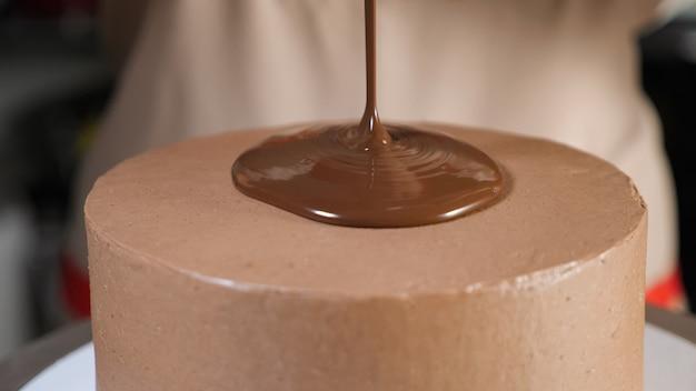 De banketbakker versiert chocoladecake met vloeibare chocolade die het op de bovenkant van de cake giet. close-up bekijken.