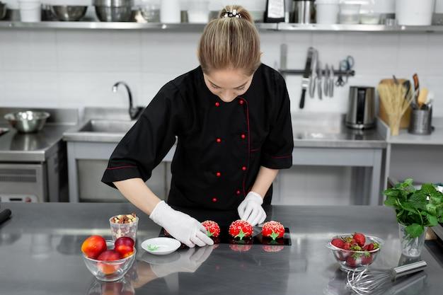 De banketbakker versiert de rode moussecake als een aardbei.