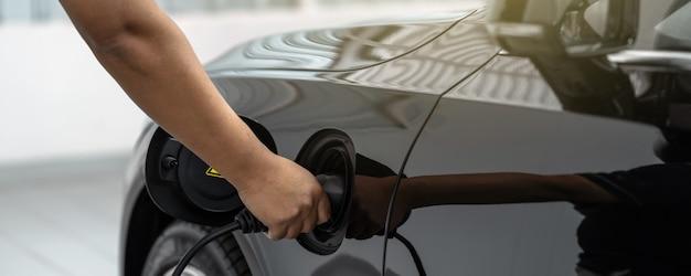 De banner van de hand van de close-up aziatische technicus laadt de elektrische auto of ev in het onderhoudscentrum op