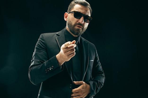 De barded man in een pak bij black Premium Foto