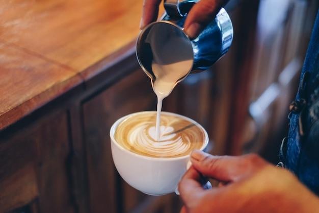 De barista gietende melk van de hand op de vorm van de koffie latte bloem in kop