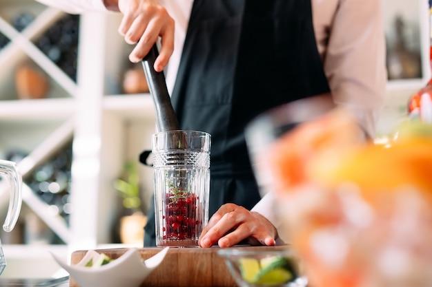 De barman bereidt een bessencocktail op het terras van het restaurant.