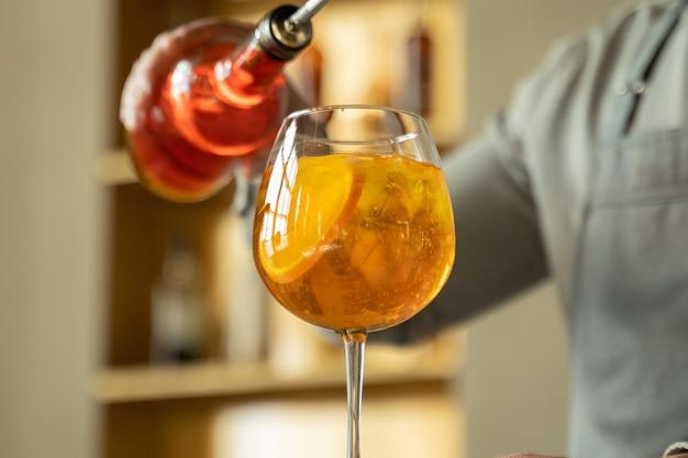De barman bereidt een cocktail en giet sinaasappelsiroop in een glas