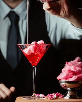 De barman bereidt zoete katoenen cocktail in martini-glas