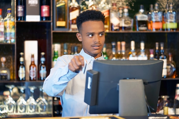 De barman bij de kassa
