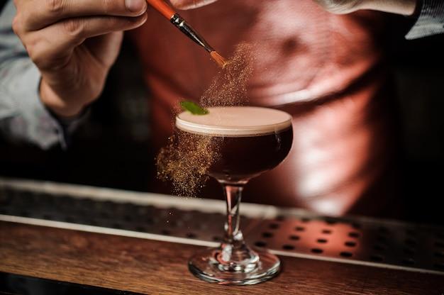De barman decoreert de cocktail met een gouden poeder