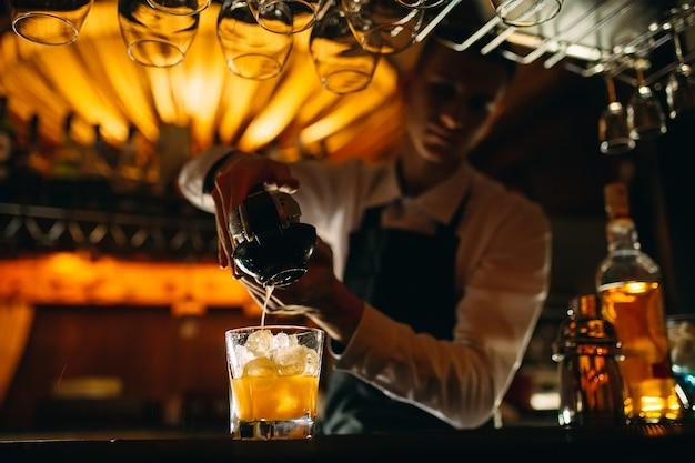 De barman drukt citrusvruchtensap in een cocktail