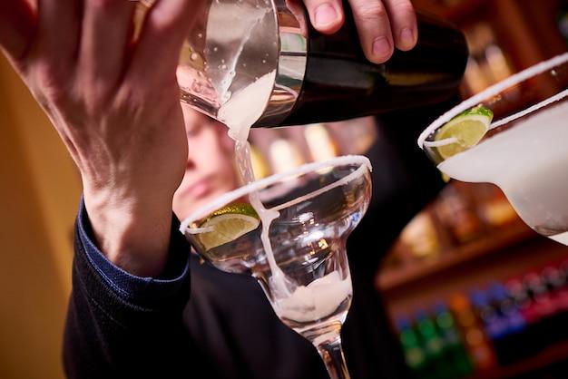 De barman giet cocktails in glazen in nachtclub.