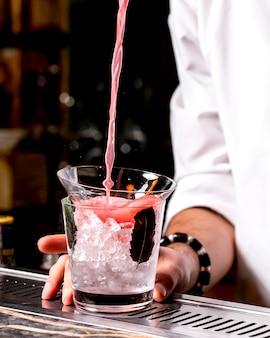De barman giet roze cocktail in glas dat in glas met ijs wordt geplaatst