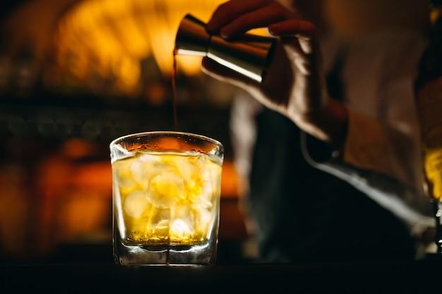 De barman giet whisky op de bar