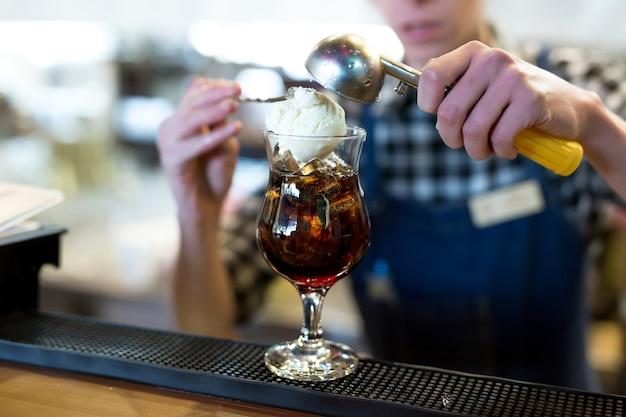 De barman in het restaurant doet een bolletje ijs in een glas met een cocktail.