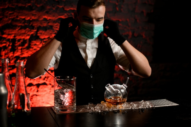 De barman in masker met zwarte handschoenen drinkt het voorbereidingen treffen om cocktail in speciale fles te maken