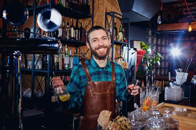 De barman lacht terwijl hij aan de bar een cocktail maakt