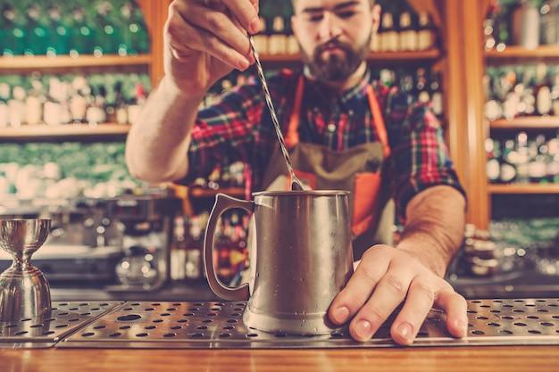 De barman maakt een alcoholische cocktail aan de bar aan de barruimte