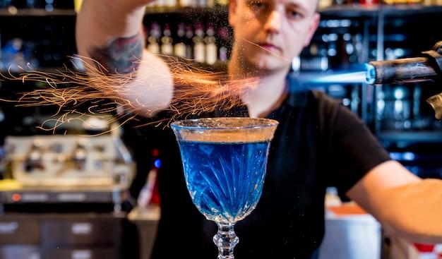 De barman maakt een cocktail met een vuurshow aan de bar. barman op het werk. een restaurant. nachtleven