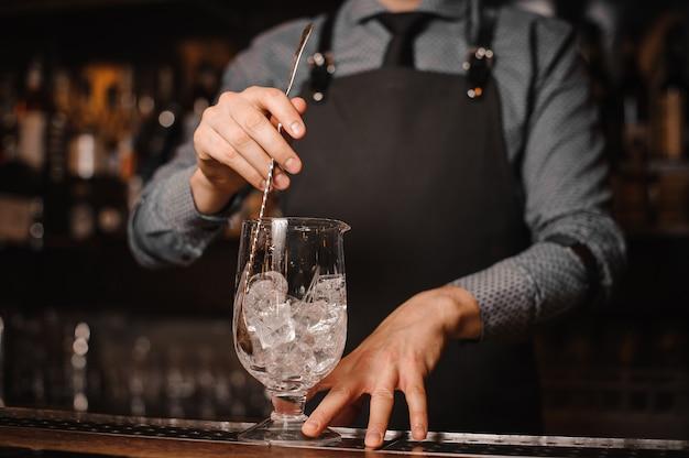 De barman maakt een cocktail met ijs