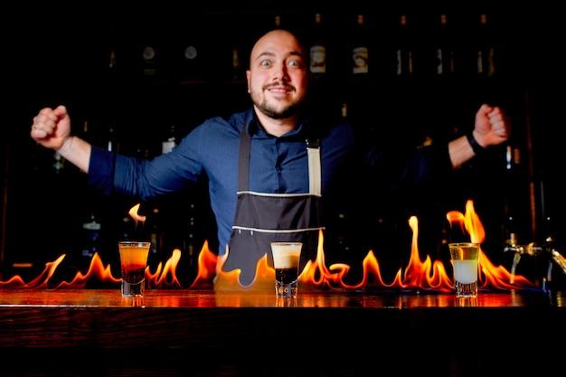 De barman maakt een hete alcoholische cocktail en ontsteekt de bar