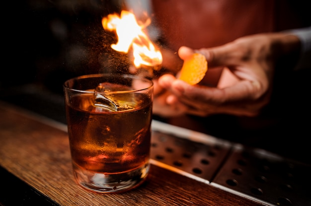 De barman maakt vlam boven cocktail dicht omhoog