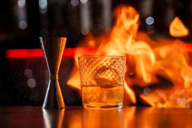 De barman maakt vlam over een cocktail met sinaasappelschil close-up.