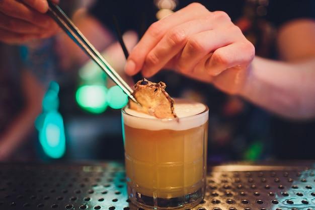 De barman maakt vlam over een cocktail met sinaasappelschil dicht omhoog.