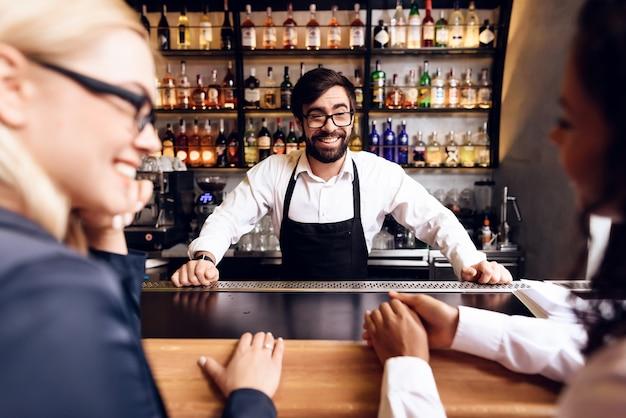 De barman met een baard bereidde een cocktail aan de bar.