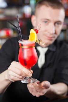 De barman overhandigt een vers bereide cocktail