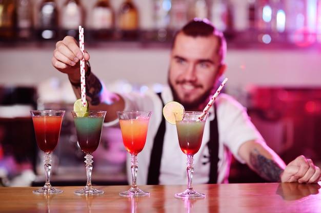 De barman plaatst de buizen voor cocktails in de bereide alcoholische dranken en glimlacht tegen de nachtclub