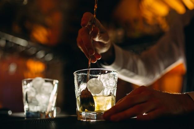 De barman roert een lepel whisky met ijs in een glas