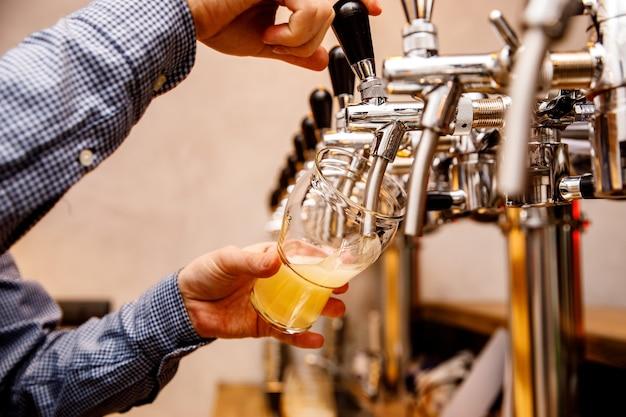 De barman schenkt vers licht bier uit de tap in de pub